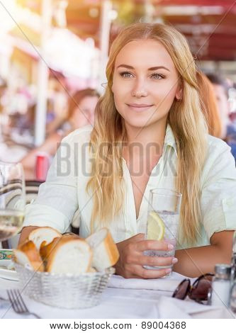 Portrait of beautiful blond woman sitting at outdoors cafe and drink water with lemon, healthy nutrition, traveling to Italy, Europe