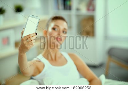 Happy woman taking a photo of herself with her mobile phone in a bedroom