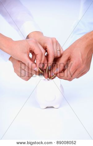 Putting coin into the piggy bank, isolated