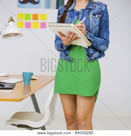 Woman working at desk In a creative office, writting a note