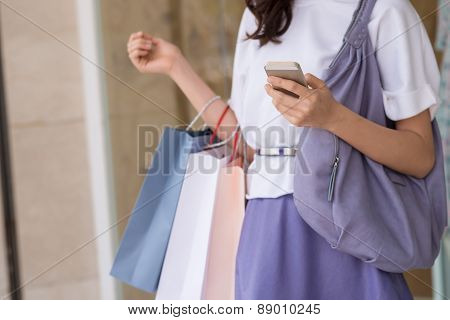 Woman with smartphone and paper-bags