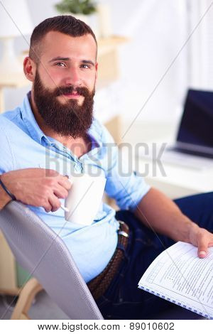 Young man sitting with laptop and a tea cup at home.