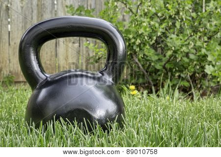 heavy iron black kettlebell on green grass in backyard - outdoor fitness concept