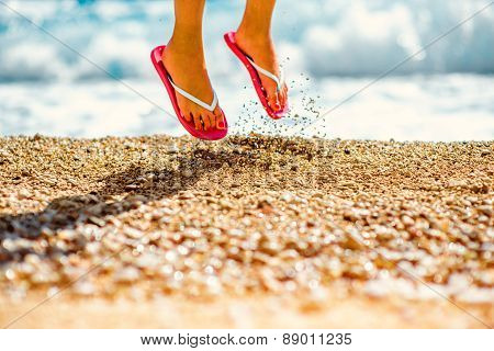 Jumping in slippers on the beach