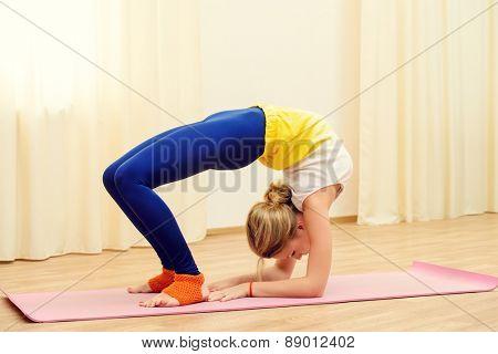 Slender athletic girl doing yoga exercises indoor. Backbend.