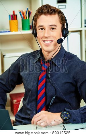 Friendly smiling young man customer service worker.  Call center male operator with phone headset working at the office.