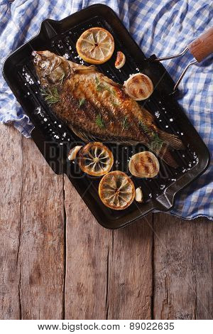Grilled Carp With Lemon In A Pan , Vertical Top View Closeup