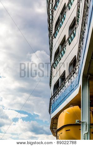 Side Of Cruise Ship Over Yellow Lifeboat