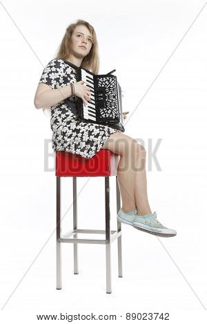 Teenage Girl Sits On Red Stool In Studio With Accordion