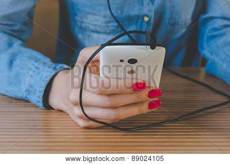 Vintage Photo Girl In A Denim Shirt, Which Listens To Music On The Phone