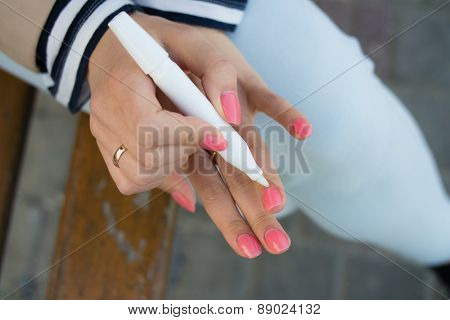 Girl Caring For Cuticles While Sitting On A Bench In The Street