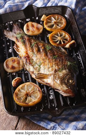 Fish Carp With Lemon And Onion On Grill Pan, Vertical