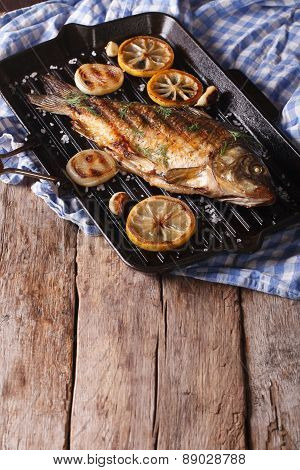 Fried Carp With Lemon, Onion And Spices On The Grill Pan