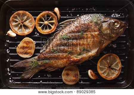 Carp With Lemon, Onion And Spices On A Black Grill Pan, Top View