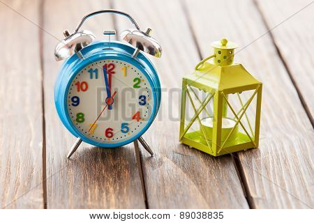 Retro Alarm Clock And Decorate Lamp On Wooden Table.