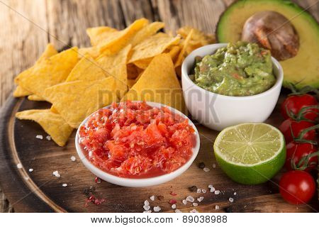 Green Guacamole with nachos and avocado on stone background