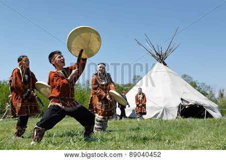 Men And Women Dancing With A Tambourine On The Grass On A Background Yaranga. Kamchatka, Russia