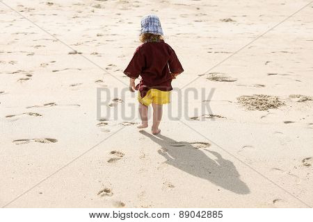 Child Leaving Small Steps In The Sand, Playing Barefoot