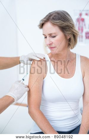 Doctor doing an injection to his patient in medical office