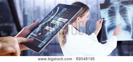 Man using tablet pc against room with large window looking on city