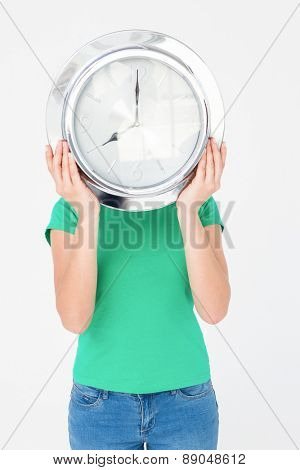 Brunette holding wall clock and hiding her face on white background