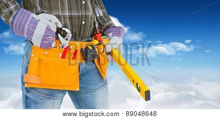Handyman holding spirit level against bright blue sky with clouds