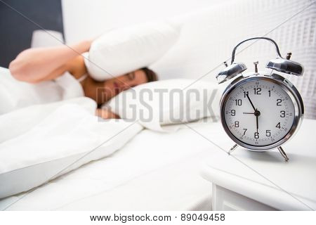 Woman covering ears with pillow at home in the bedroom