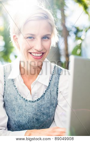 Pretty blonde woman using her laptop in the park
