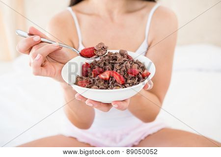 Pretty brunette holding a cereal bowl on bed at home