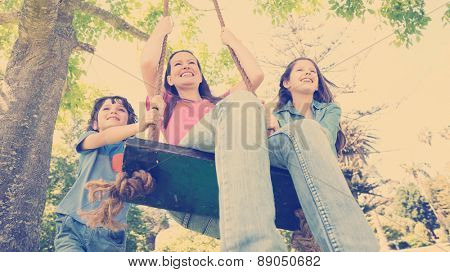 Low angle view of kids pushing mother on swing in playground