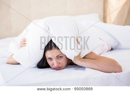 Pretty brunette looking at camera and hiding under the pillow at home