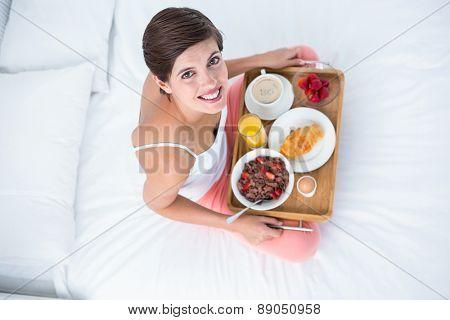 Happy brunette having her breakfast in bed at home in he bedroom