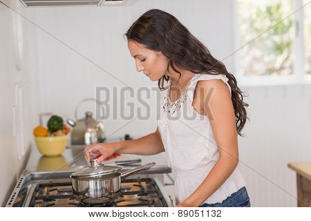 Beautiful brunette looking at saucepan in the kitchen