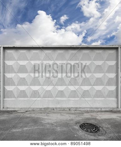 Dark Urban Road And Blue Sky Behind Gray Concrete Fence