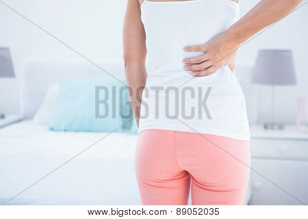 Woman with back pain at home in the bedroom