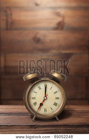 Brown old style alarm clock on wooden background