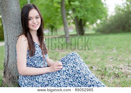 Summer girl portrait. Asian woman smiling happy on sunny summer day outside in park