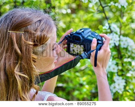Girl photographs blossoming cherry tree. Romantic style.