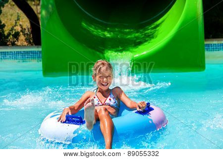 Child on water slide at aquapark. Summer holiday. Green and blue.