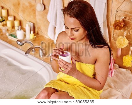 Woman applying moisturizer at bathroom. Small box in hands.