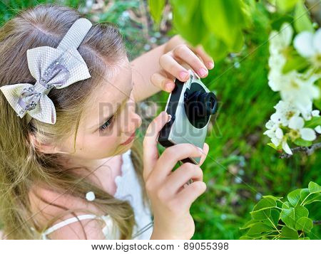 Little girl photographs blossoming tree at spring. Romantic style.