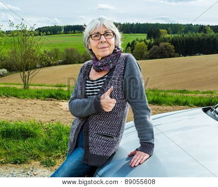 Senior Woman With Car And Thumbs Up