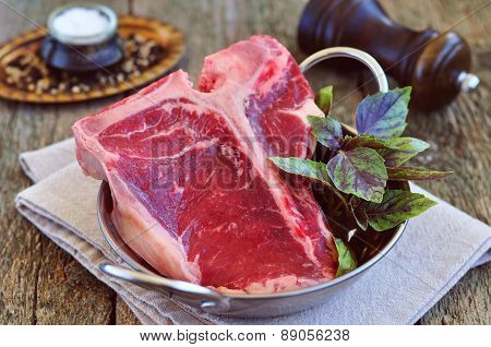 Juicy raw beef t-bone steak on wooden table