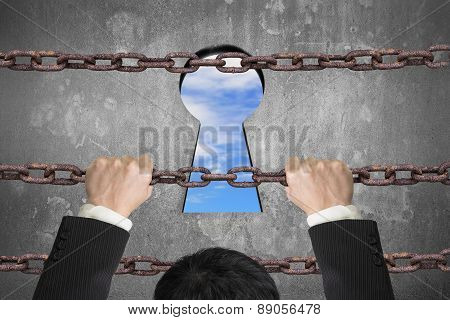 Businessman Climbing On Iron Chain For Keyhole With Sky Clouds