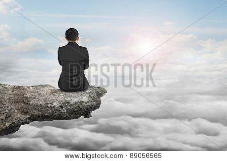Rear View Businessman Sitting On Cliff With Natural Daylight Cloudscape