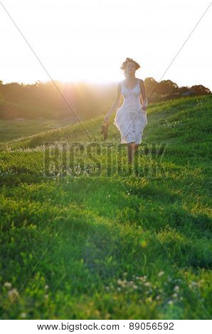 Girl runing on a green summer meadow