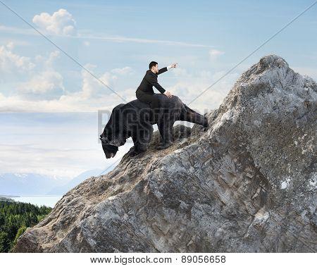 Businessman Riding Black Bear Climbing On Mountain Peak With Sky