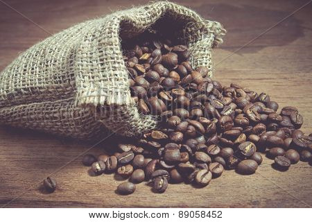 Coffee Beans In A sack On A Wooden Background.
