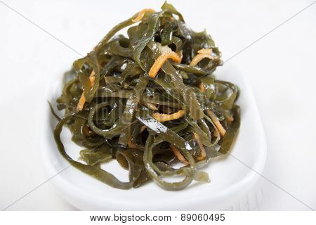 Kelp Salad With Carrots On A White Plate And White Background.