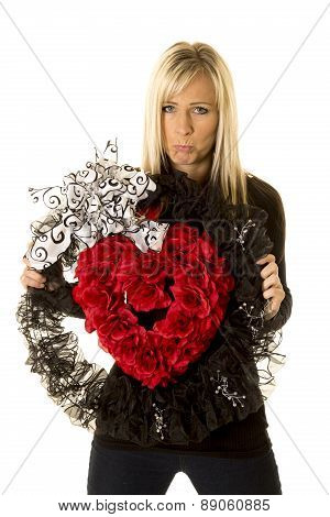 Woman Holding Heart Wreath Sad